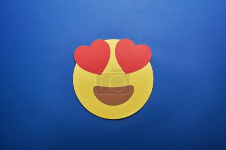 top view of in love emoji on blue background