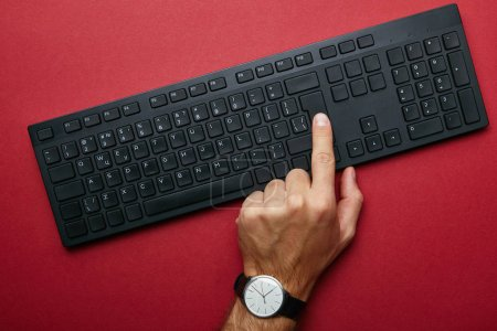 Top view of male hand pushing button on black computer keyboard on red background