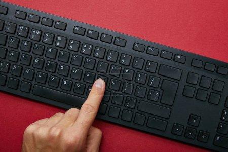 Photo pour Vue recadrée de l'homme appuyant sur le bouton sur le clavier de l'ordinateur noir sur fond rouge - image libre de droit