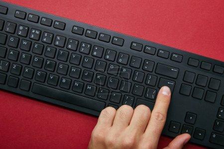 Photo pour Vue de dessus de l'homme en poussant le bouton sur le clavier de l'ordinateur noir sur fond rouge - image libre de droit