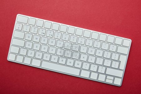Top view of white computer keyboard on red background