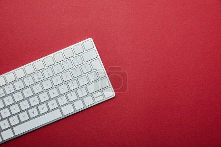 Vue du dessus du clavier d'ordinateur blanc sur fond rouge avec espace de copie