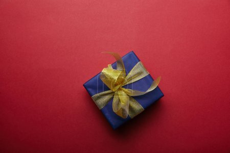 Top view of wrapped gift with golden ribbon on red background