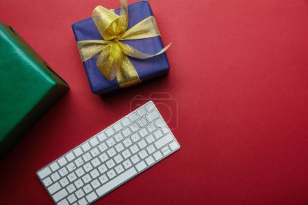 Photo for Cropped view of wrapped gifts near white computer keyboard on red background - Royalty Free Image
