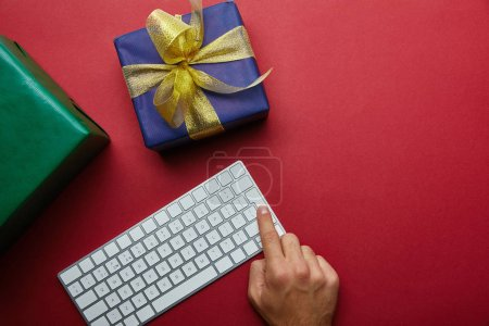 Top view of man finger pushing button on computer keyboard near colourful gifts on grey background