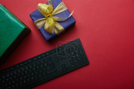 Foto de Vista recortada de regalos cerca de teclado negro sobre fondo rojo - Imagen libre de derechos