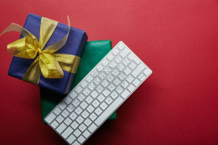 Top view of colourful presents near white computer keyboard on red background