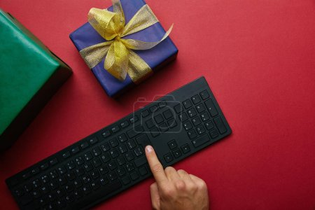 Cropped view of man pushing button on computer keyboard near wrapped boxes on red background