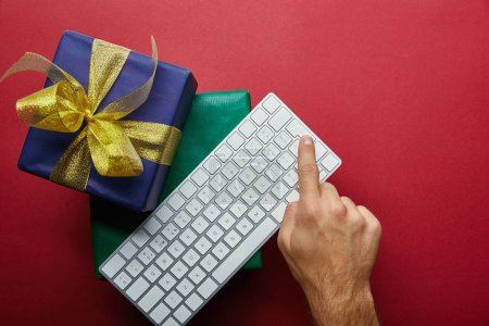 Photo for Top view of man pushing button on computer keyboard near presents on red background - Royalty Free Image