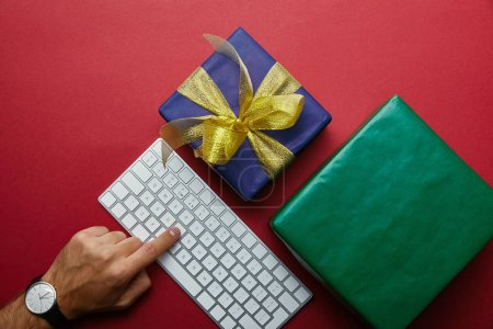 Top view of man pushing button on white computer keyboard near colourful gifts on red background