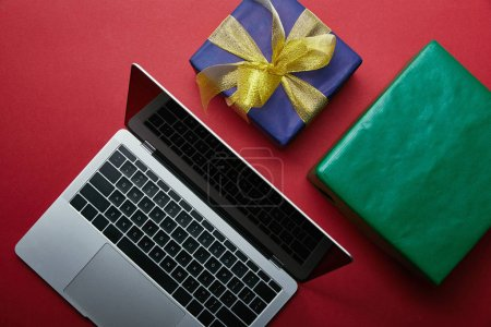 Photo for Cropped view of laptop near wrapped gifts on red background - Royalty Free Image