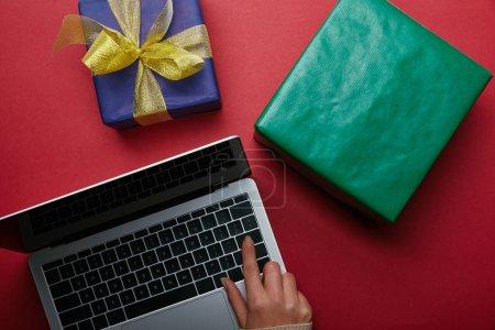 Foto de Vista superior de la mujer utilizando el teclado del ordenador portátil cerca de regalos sobre fondo rojo - Imagen libre de derechos