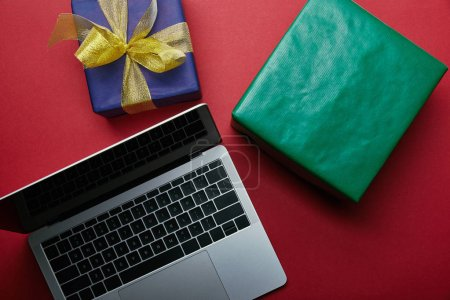 Cropped view of laptop with laptop keyboard near wrapped presents on red background