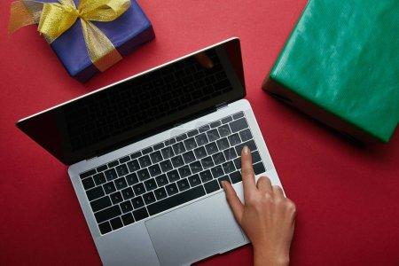 Foto de Vista superior del botón de empuje de mujer en el teclado del ordenador portátil cerca presenta sobre fondo rojo - Imagen libre de derechos