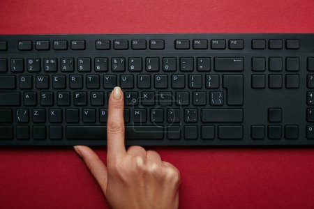 Cropped view of woman pushing button on black computer keyboard on red background