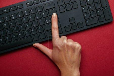 Photo pour Vue de dessus de femme en poussant le bouton sur le clavier de l'ordinateur noir sur fond rouge - image libre de droit