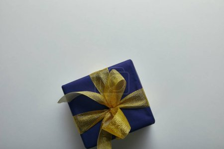 Top view of gift wrapped in blue wrapping paper with yellow ribbon on grey background