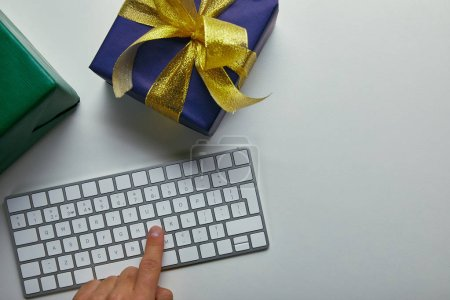 Cropped view of man pushing button on computer keyboard near colourful presents on grey background