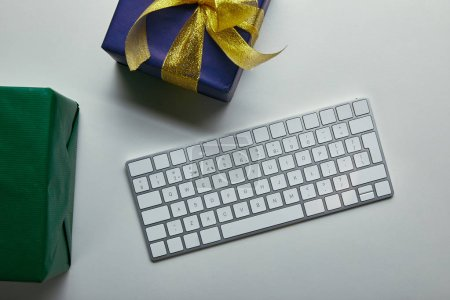 Cropped view of presents near computer keyboard on grey background