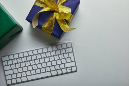 Photo for Cropped view of gifts near white computer keyboard on grey background - Royalty Free Image