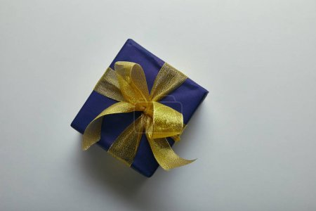 Top view of wrapped present with yellow ribbon on grey background