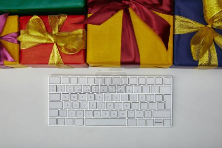 Photo for Top view of colourful gifts near computer keyboard on white background - Royalty Free Image