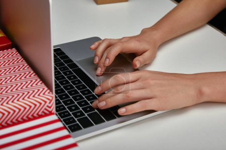 Cropped view of woman hands typing on laptop keyboard