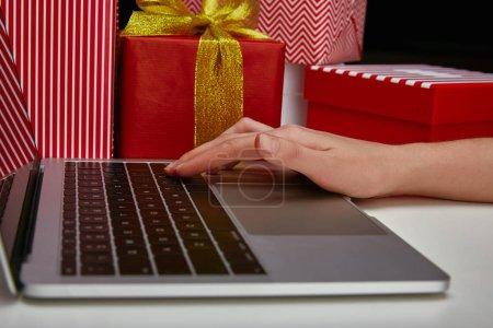 Foto de Vista recortada de mujer usando la laptop cerca de regalos envueltos - Imagen libre de derechos