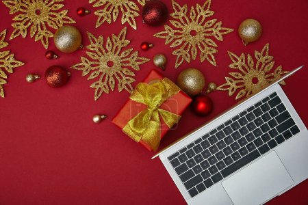 Top view of laptop near wrapped present and decorations on red background