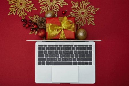 Top view of laptop near wrapped gift and decorations on red background