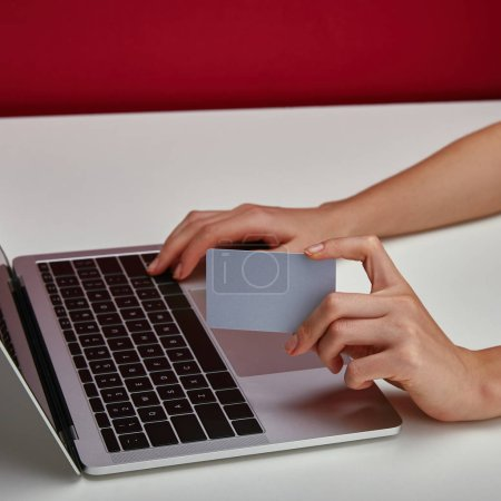 Cropped view of woman holding credit card in hand and using laptop