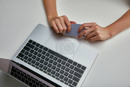 Top view of woman holding credit card near laptop on white background