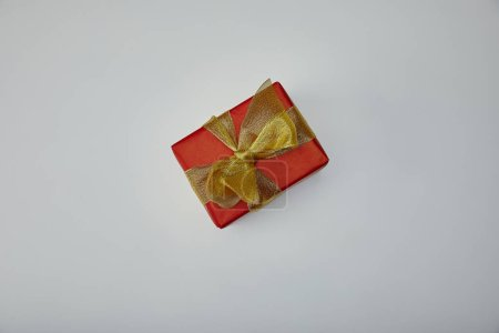 Top view of wrapped gift with golden ribbon isolated on grey background