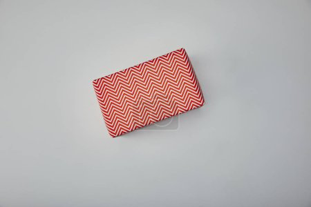 Photo for Top view of wrapped present on grey background - Royalty Free Image