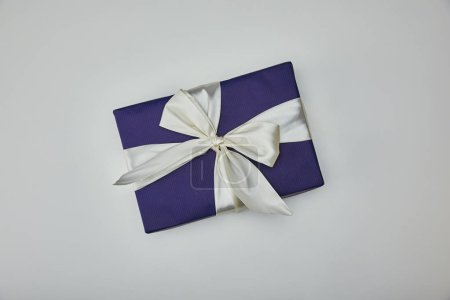 Top view of wrapped present with white ribbon isolated on grey background