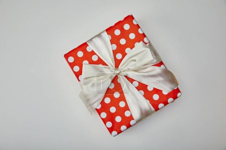 Top view of wrapped present with bow isolated on grey background