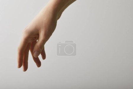close up of woman with hand into pure water, isolated on grey with copy space