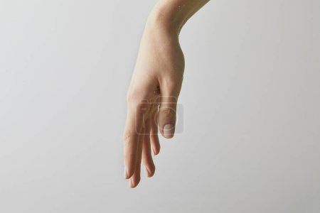 cropped view of woman putting hand into water, isolated on grey