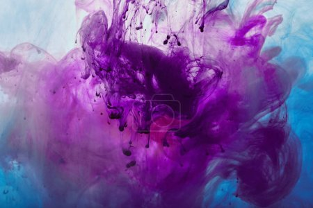 close up view of purple and blue mixing paint swirls