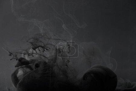Photo pour Tourbillons sombres de peinture sur fond gris - image libre de droit
