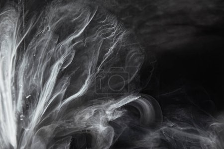 abstract flowing swirls of grey paint on black background