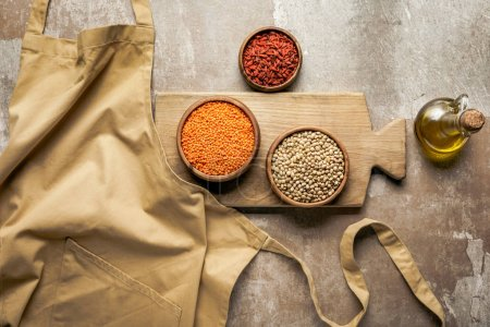 flat lay of apron, legumes, goji berries on wooden board with rustic background