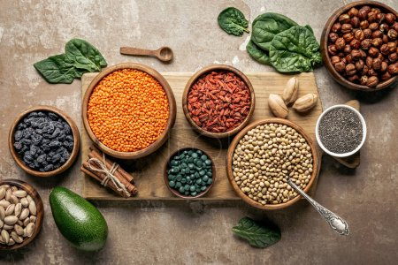 Photo for Top view of wooden board with legumes, goji berries and healthy ingredients with rustic background - Royalty Free Image