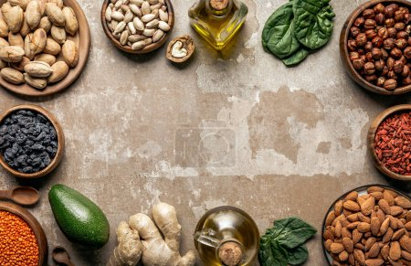 frame made of nuts, superfoods and healthy ingredients on rustic background with copyspace