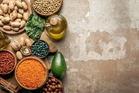 Photo for Top view of superfoods, legumes, olive oil and healthy ingredients on rustic background with copy space - Royalty Free Image