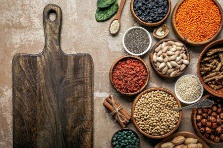 Photo pour Vue du dessus de la planche en bois, superaliments, légumineuses et ingrédients sains sur fond rustique - image libre de droit