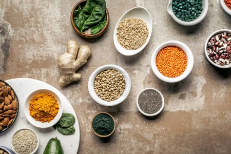 flat lay of superfoods, spices and legumes on textured rustic background