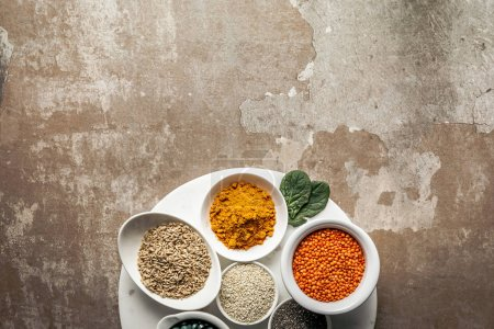 top view of red lentils, oat groats and turmeric on textured rustic background with copy space