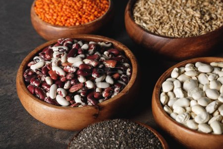 Photo for Variety of beans, lentils and oat groats in wooden bowls on table - Royalty Free Image