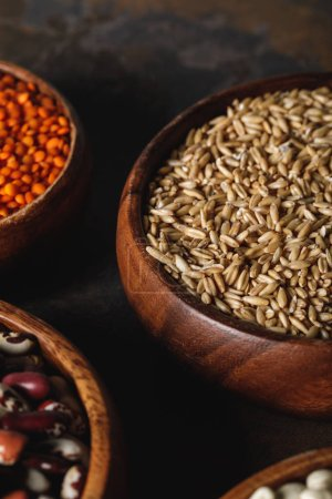 close up of oat groats in wooden bowl on table